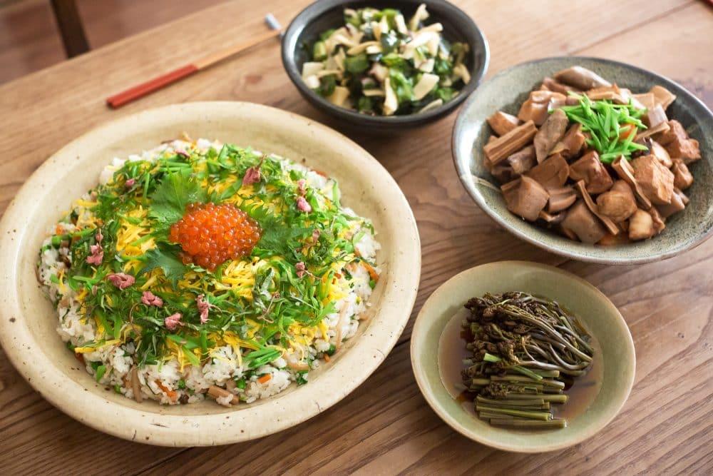 お皿に盛られた料理の数々。みずみずしい旬の食材たちと、ちらし寿司の色彩が、食卓に彩りを添える。