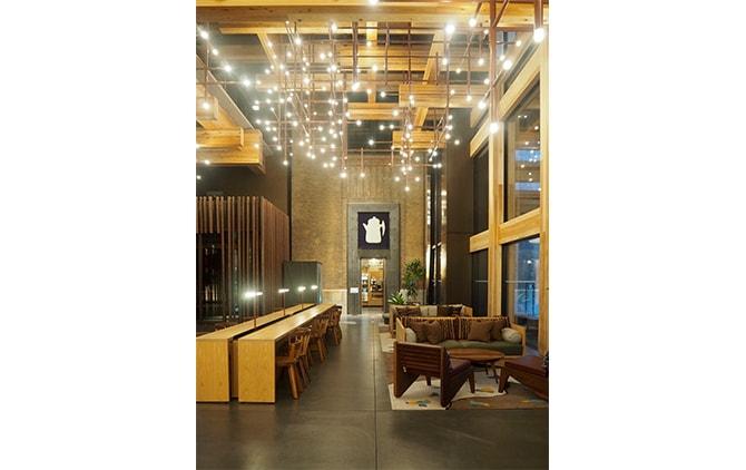 24時間オープンの1階ロビー。天井は隈研吾建築らしい木組み。左手長テーブルにはコンセントが並ぶ。奥は日本初出店となるスタンプタウン・コーヒー・ロースターズ(朝7時オープン)。エントランス上に掛かるタペストリーは柚木沙弥郎によるもの。