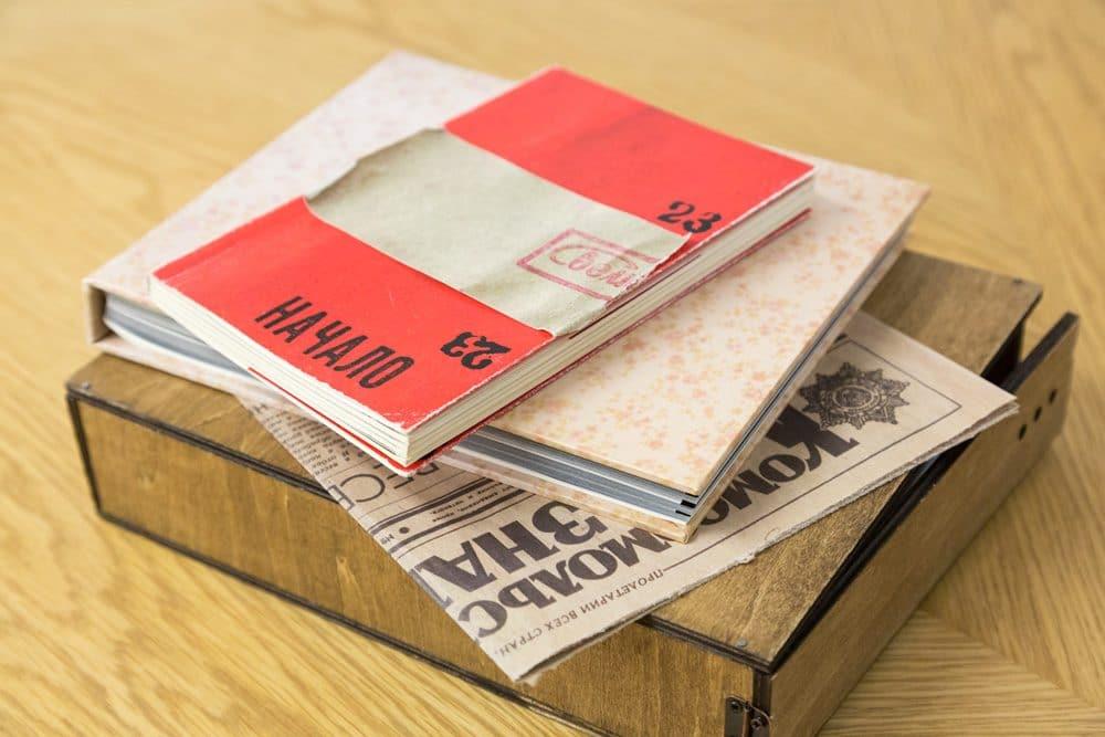 手製の写真集『Exposure』に収められた2冊の写真集と、新聞の複製。